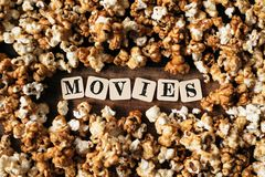 Fresh popcorn background with MOVIES word. On a wooden table Stock Photo