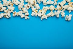Fresh popcorn on a blue background, empty space for text stock photography