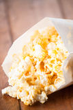 Fresh popcorn in paper bag on table Stock Photos