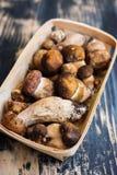 Fresh porcini. Mushrooms in a basket, wooden background Stock Images