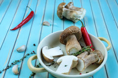 Fresh porcini mushrooms and herbs in frying pan on wooden table Stock Photos