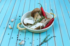 Fresh porcini mushrooms and herbs in frying pan on wooden table Stock Images