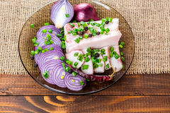 Fresh pork fat, with red hot chili peppers, green and purple onions. And  peas allspice beautifully laid out on a glass plate on the background of old boards Stock Image
