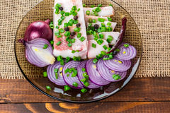 Fresh pork fat, with red hot chili peppers, green and purple onions. And  peas allspice beautifully laid out on a glass plate on the background of old boards Royalty Free Stock Photography