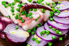 Fresh pork fat, with red hot chili peppers, green and purple onions. And  peas allspice beautifully laid out on a glass plate on the background of old boards Stock Photography