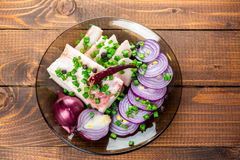 Fresh pork fat, with red hot chili peppers, green and purple onions. And  peas allspice beautifully laid out on a glass plate on the background of old boards Royalty Free Stock Photos
