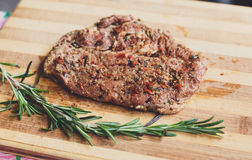 Fresh pork meat on a cutting board. Fresh pork steak ready for BBQ cooking. Raw meat on a cutting board with rosemary leaf. Raw pork meat on wood, closeup Royalty Free Stock Photos