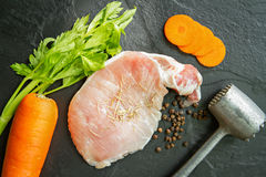 Fresh pork meat with pepper, rosemary, carrot, celery  and meat. Hammer on black stone Stock Image