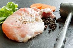 Fresh pork meat with pepper, rosemary, carrot, celery  and meat. Hammer on black stone Stock Photos