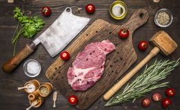 Fresh pork steak on a cutting board with rosemary, a hammer for beating the meat and ax for meat, seasoning herbs on wooden ru stock photos