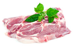 Fresh pork steaks and basil Royalty Free Stock Images