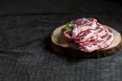 Fresh pork on a wooden board, dark background, copy space. Fresh pork on a wooden board, copy space Stock Photo