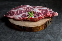 Fresh pork on a wooden board, dark background. And mint Royalty Free Stock Photos