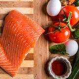 Fresh portion of fresh salmon fillet with. Top view of Fresh salmon fillet with eggs and tomato and other vegetable Royalty Free Stock Photos