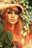 Fresh portriat of sexy redhair lady in leaves with wreath of hop Royalty Free Stock Images