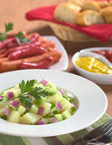 Fresh Potato Salad. With cucumber, red and green onion made with an oil dressing with barbecued sausages, mustard, ketchup and baguette in the back (Selective stock image