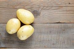 Fresh potato on wooden table Stock Photo