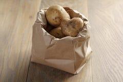 Fresh potatoes in kraft paper bag on oak table Stock Photo