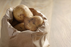 Fresh potatoes in kraft paper bag on oak table Stock Photos