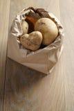 Fresh potatoes in kraft paper bag on oak table Royalty Free Stock Images