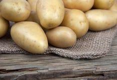 Fresh Potatoes lying on a bag on old wood Royalty Free Stock Image