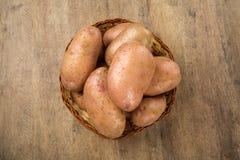 Fresh potatoes on rustic wooden background. Batata asterix em uma cesta sobre uma mesa stock photos