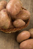 Fresh potatoes on rustic wooden background. Batata asterix em uma cesta sobre uma mesa royalty free stock photos