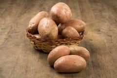 Fresh potatoes on rustic wooden background. Batata asterix em uma cesta sobre uma mesa royalty free stock image