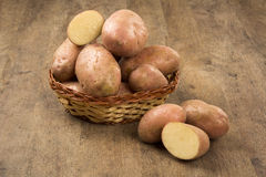 Fresh potatoes on rustic wooden background. Batata asterix em uma cesta sobre uma mesa royalty free stock photo