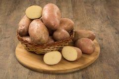 Fresh potatoes on rustic wooden background. Batata asterix em uma cesta sobre uma mesa stock images