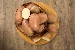 Fresh potatoes on rustic wooden background. Batata asterix em uma cesta sobre uma mesa stock photo