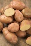 Fresh potatoes on rustic wooden background. Batata asterix em uma cesta sobre uma mesa stock image
