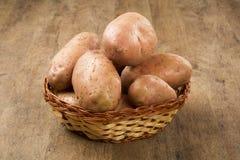 Fresh potatoes on rustic wooden background. Batata asterix em uma cesta sobre uma mesa royalty free stock images