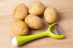 Fresh potatoes with vegetable peeler Royalty Free Stock Photos