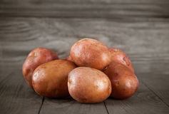 Fresh potatoes on wooden board Royalty Free Stock Photos
