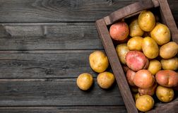 Fresh potatoes in a wooden box. On wooden background royalty free stock photos