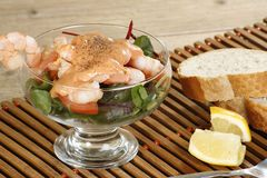 Fresh prawn cocktail. Fresh king prawn cocktail with bread slices and lemon wedges Royalty Free Stock Photo