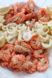 Prawns and Calamari. Fresh prawns and calamari served as a starter with sliced lemon stock images