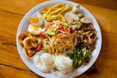 Papaya salad food selection. Fresh prepared asian SomTam papaya salad selection served with glass noodle,egg, pork cracklings, bamboo shots, fish, sausage and royalty free stock photo
