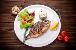 Fresh prepared dorado or sea bream fish with lemon, herbs on woo Stock Photos
