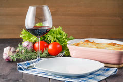 Fresh prepared lasagne with ingredients on table Stock Image