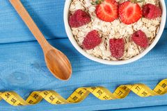 Oat flakes or oatmeal with fruits and tape measure, healthy lifestyle and nutrition concept. Fresh prepared oat flakes or oatmeal with fruits and centimeter Royalty Free Stock Image