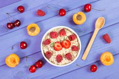 Fresh prepared oat flakes and oatmeal with fruits, healthy lifestyle and nutrition. Fresh prepared oat flakes and oatmeal with fruits in glass bowl, concept of Stock Photography