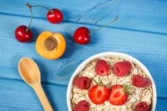Fresh prepared oat flakes and oatmeal with fruits, healthy lifestyle and nutrition. Fresh prepared oat flakes and oatmeal with fruits in glass bowl, concept of Royalty Free Stock Images