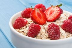 Fresh prepared oat flakes or oatmeal with strawberries and raspberries, healthy lifestyle and nutrition. Fresh prepared oat flakes or oatmeal with strawberries Royalty Free Stock Images