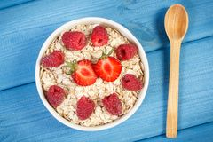 Fresh prepared oat flakes or oatmeal with strawberries and raspberries, healthy lifestyle and nutrition. Fresh prepared oat flakes or oatmeal with strawberries Stock Image