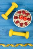Fresh oatmeal with strawberries and raspberries, centimeter and dumbbells, healthy lifestyle and nutrition. Fresh prepared oatmeal with strawberries and Royalty Free Stock Photo