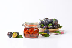 Fresh and preserved plums Stock Images