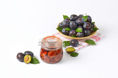 Fresh and preserved plums Stock Photography