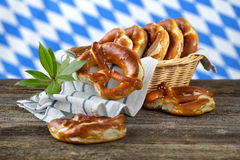 Fresh pretzels. Fresh Bavarian pretzels in a breadbasket on a wooden table, in the background the white-blue flag of Bavaria Royalty Free Stock Image